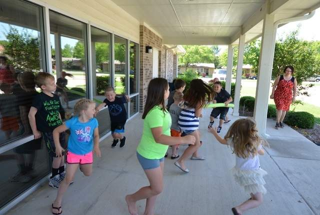 "Children play the ""fish game,"" which involves dodging pool noodles, Thursday morning at the Bonham House Authority TEAM Center building during the Texoma Council of Governments Summer Youth Program. (Alex Maxwell / Herald Democrat)"