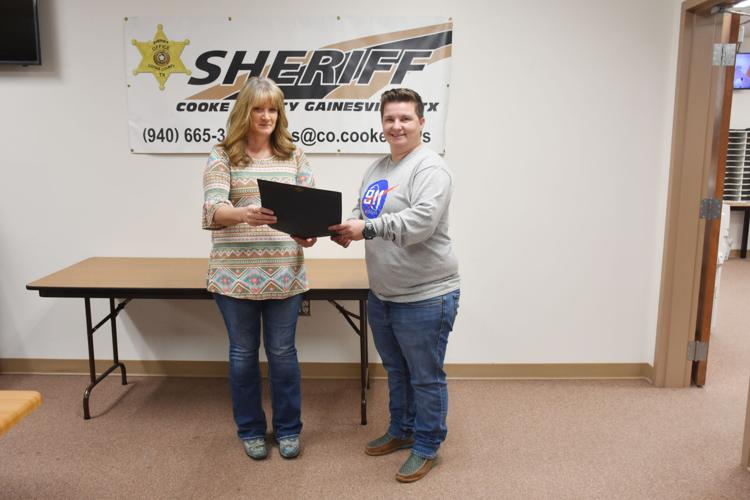 Cooke County Dispatch Supervisor Linda Jones presents an award to dispatcher Hannah McKinney, right. Megan Gray-Hatfield/GDR