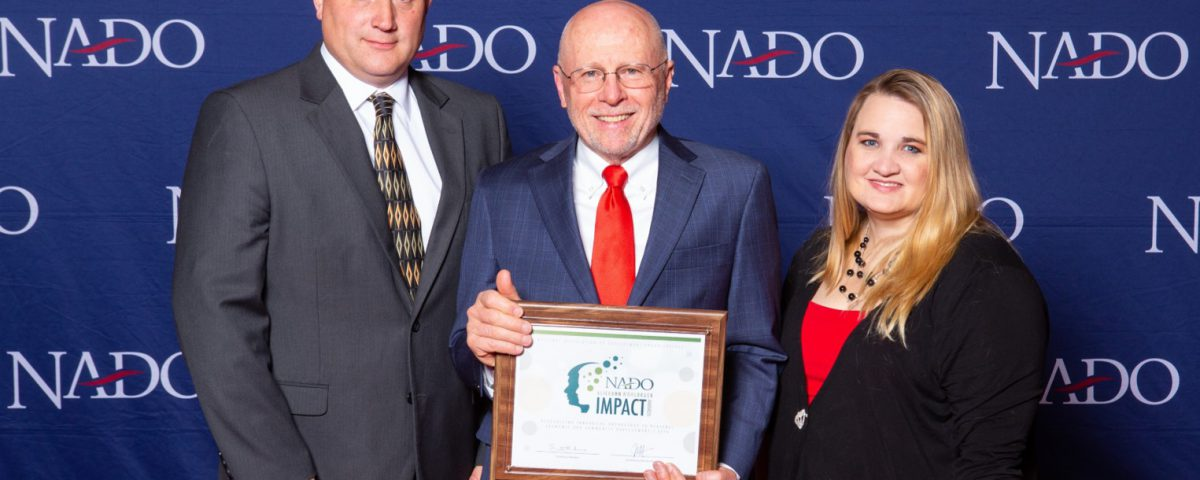 TCOG Executive Director, Eric Bridges (left), with NADO 2018-19 President Scott Koons (center), and TCOG CSBG Specialist Bobbie McDonald (right) being presented with the 2019 NADO Impact Award