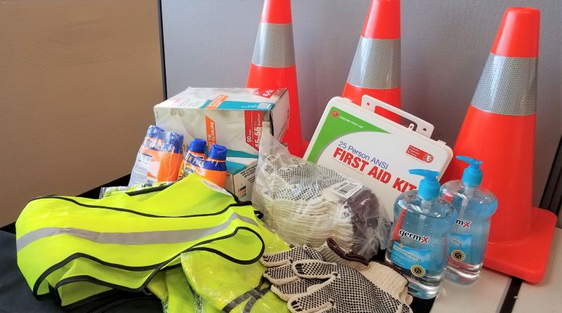 Image contains first aid kit, orange cones, sunscreen, hand sanitizer, reflective vest, gloves, and trashbags.